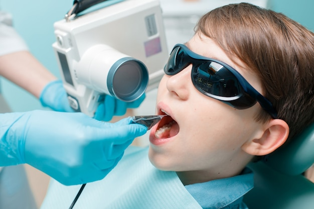 Dentist takes jaw xray patient in dental chair