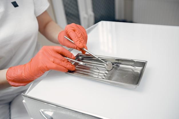 Стоматолог берет инструменты. доктор в защитных перчатках. инструмент лежит на столе