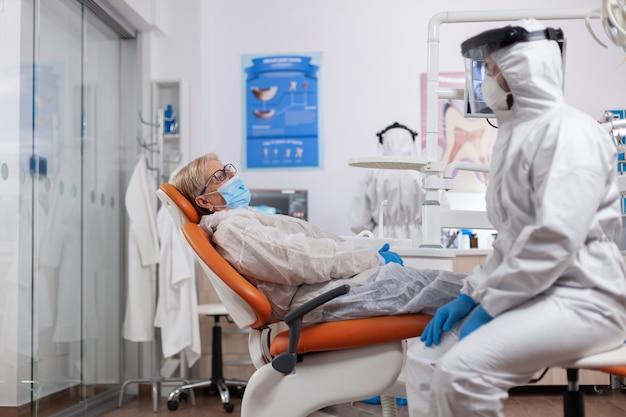 化学防護服を着た歯の衛生について話している歯科医