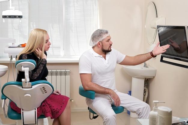 空白のモニターを指している患者と話している歯科医