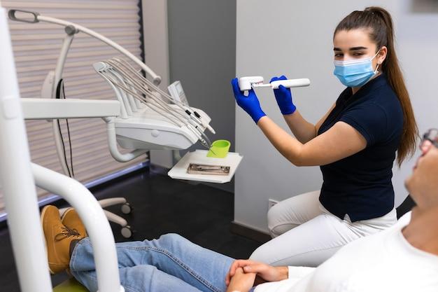 歯科医は患者に歯をきれいにする方法を教えます。