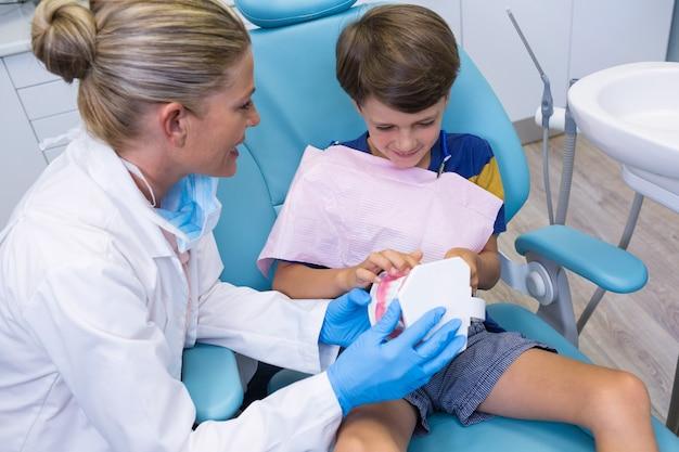 Dentist teaching boy brushing teeth on dentures
