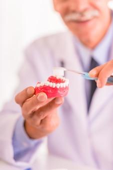 Стоматолог учит чистить зубы.