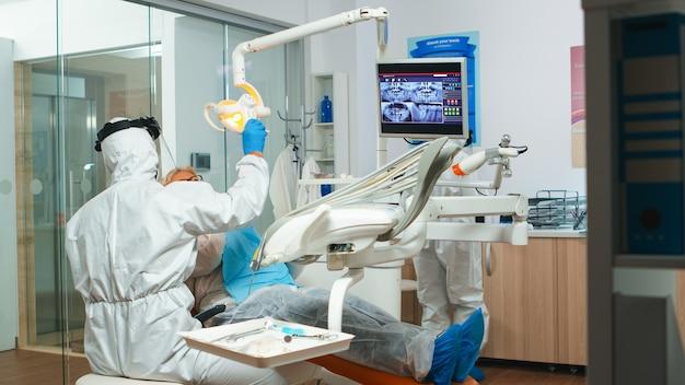 世界的大流行の際に歯科医院のランプを点灯する歯科手術の準備をしているカバーオールの歯科技工士。防護服、フェイスシールド、マスク、手袋を着用した医療チーム。