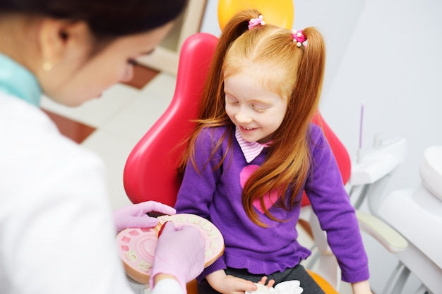 The dentist tells the child about oral hygiene