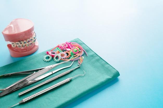 Инструменты стоматолога и ортодонтическая модель на синей поверхности