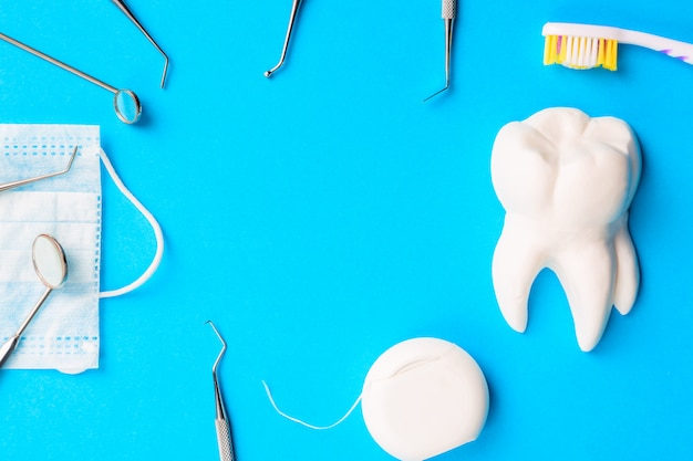 Dentist tools or instruments dental explorers, dental mirrors, toothbrush, dental floss and procedure face mask on light blue background.