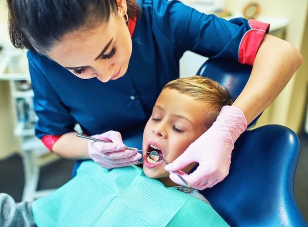 Стоматолог лечит зубы и пломбирует полость в современной клинике