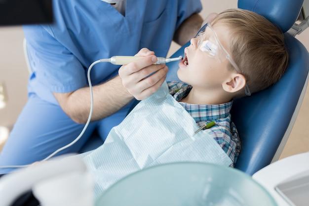 Стоматолог лечит маленького мальчика