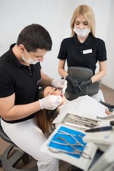 Стоматолог лечит пациента в клинике