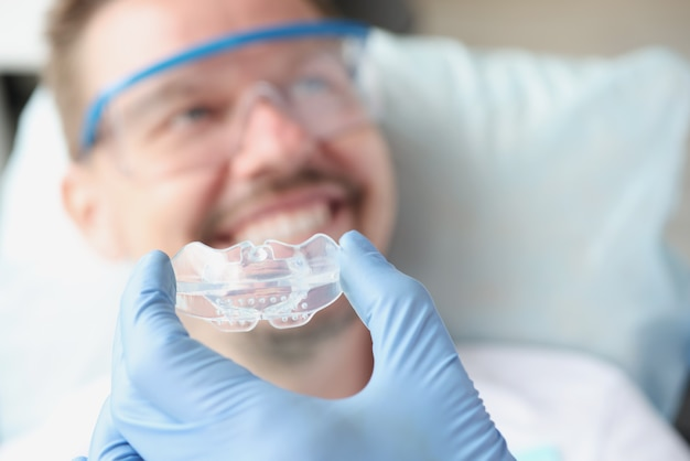 Dentist tries on silicone mouthguard to patient