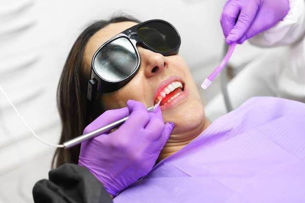 最新のダイオード歯科用レーザーを使用している歯科医。