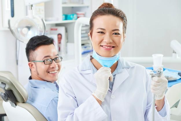 歯科医は歯科用ドリルを使用して治療