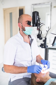 Dentist using dental microscope for treating female patient's teeth