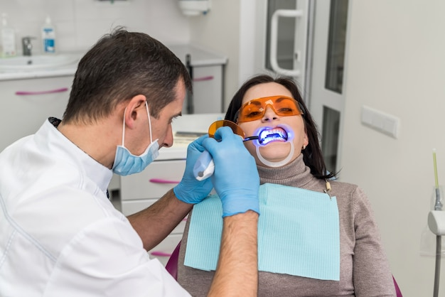 Dentist using uv lamp while treating patient's teeth