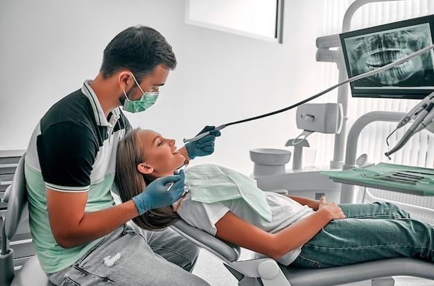 치과 의사는 그의 젊은 여성 환자의 치아를 매우 신중하게 확인하고 수리합니다. 치과 의사 사무실에서 치과 의자에 앉아 행복 한 젊은 여자.