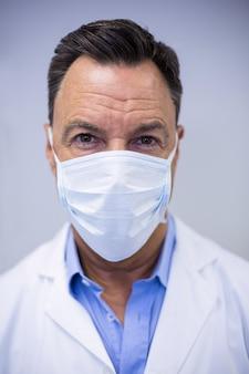 Стоматолог в хирургической маске в стоматологической клинике