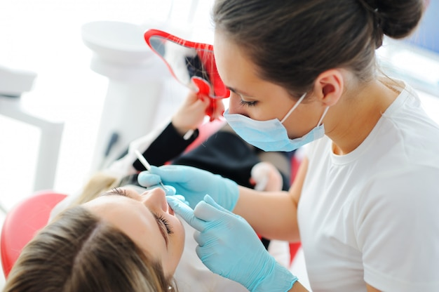 Стоматолог отбеливает зубы пациенту - привлекательная девушка