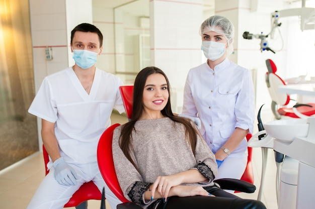 A dentist with an assistant, heals teeth to a beautiful girl.