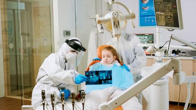 世界的大流行の際に患者の母親と話している口のx線画像の子供の患者を保持しているカバーオールを持つ歯科医。アシスタントと医師がスーツ、つなぎ服、保護スーツ、マスク、手袋を着用して話している