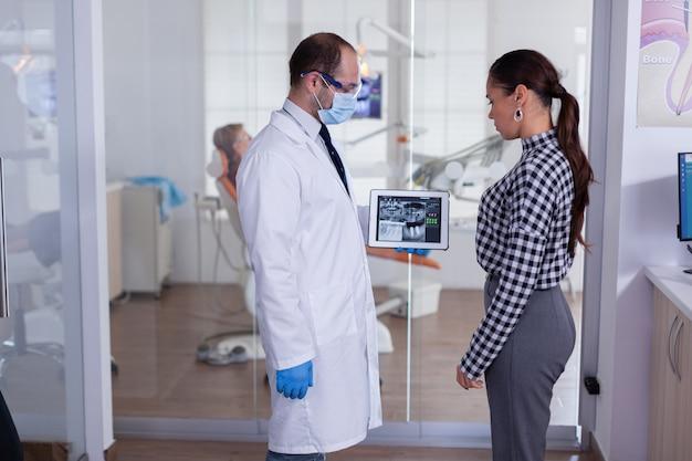 치과 전문의 리셉션에서 환자 치과 엑스레이를 보여주는 안면 마스크를 쓴 치과 의사