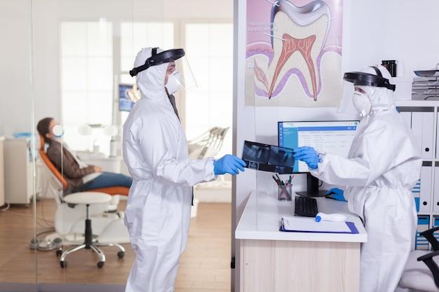 フェイスシールドとppeスーツを持った歯科医が、患者のx線を秘書から取得し、コロナウイルスによる世界的大流行の際に社会的距離を保ちます。