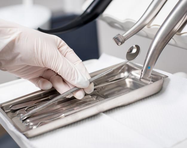 Стоматолог с рукой в перчатке выбирает стоматологический инструмент в стоматологическом кабинете