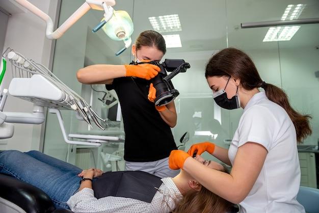 プロのショットを作る特別なカメラを持つ歯科医