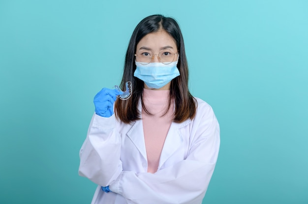 Dentist woman holding orthodontic retainer on blue screen background. dental care and healthy teeth.