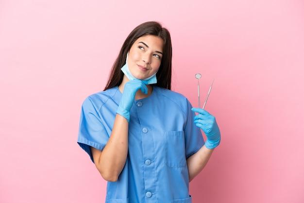 ピンクの背景に分離され、見上げるツールを保持している歯科医の女性
