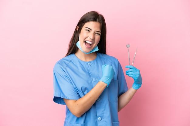 Женщина стоматолога, держащая инструменты, изолированные на розовом фоне, празднует победу