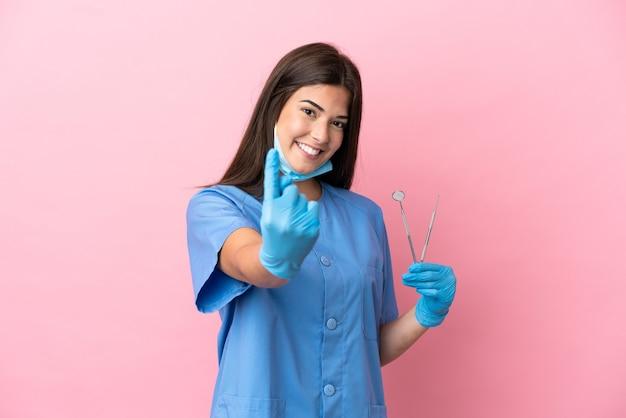 来たるジェスチャーをしているピンクの背景に分離されたツールを保持している歯科医の女性