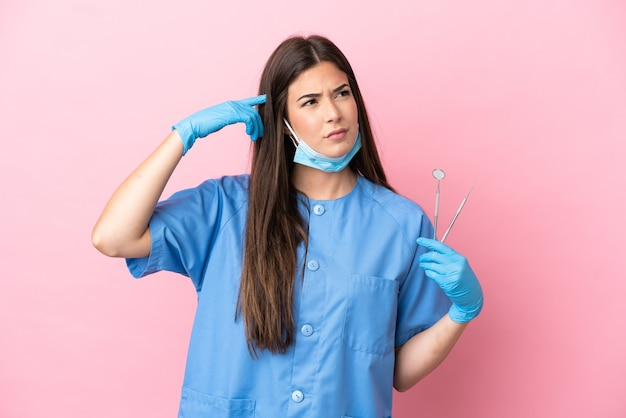 疑いと思考を持っているピンクの背景に分離されたツールを保持している歯科医の女性