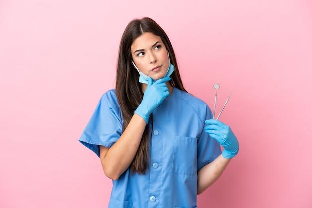 Женщина стоматолога, держащая инструменты, изолированные на розовом фоне, сомневаясь