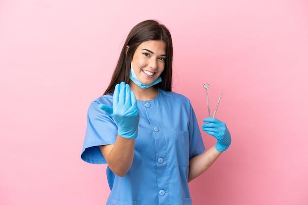 ピンクの背景に分離されたツールを保持している歯科医の女性は、手で来るように誘います。あなたが来て幸せ