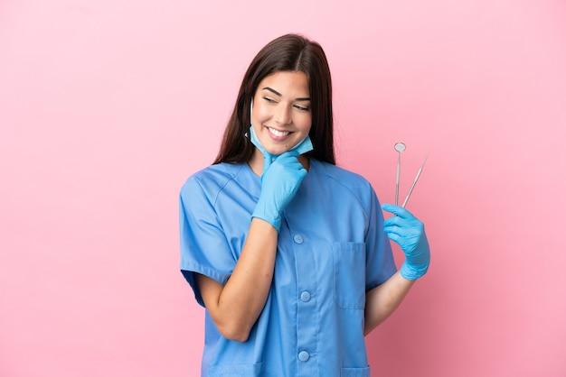 ピンクの背景に分離されたツールを保持している歯科医の女性は、横を見て笑っている