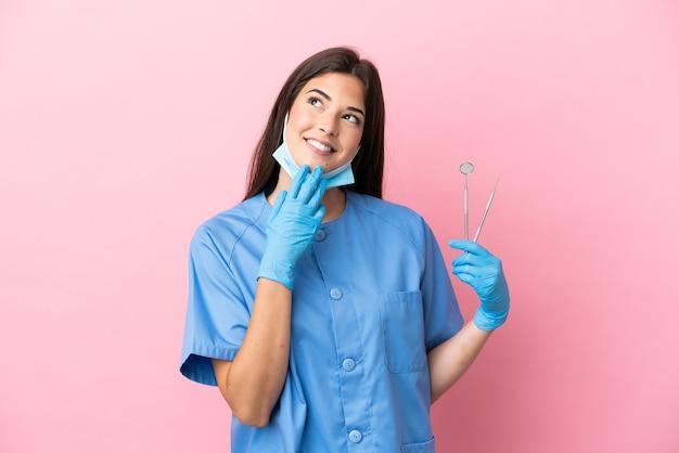Женщина стоматолога, держащая инструменты, изолированные на розовом фоне, глядя вверх, улыбаясь
