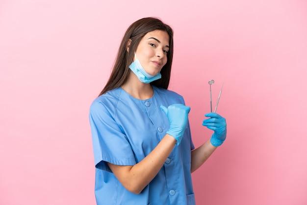 誇りと自己満足のピンクの背景に分離されたツールを保持している歯科医の女性