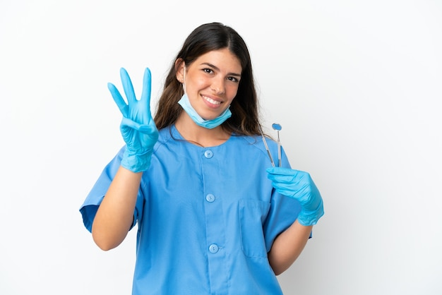 Dentist woman holding tools over isolated white background happy and counting three with fingers