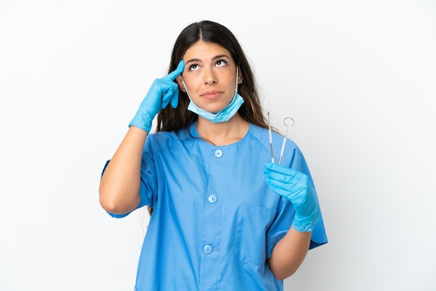 Dentist woman holding tools over isolated white background having doubts and thinking