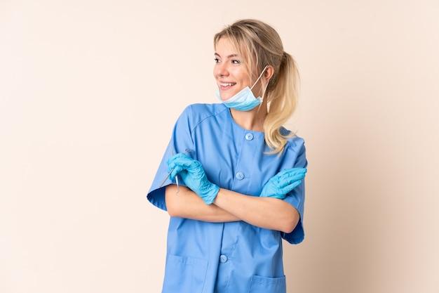 笑っている孤立した壁の上にツールを保持している歯科医の女性