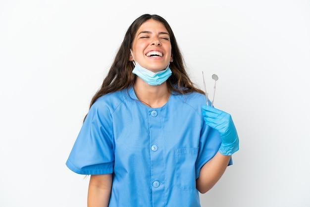 Женщина стоматолога, держащая инструменты на изолированном белом фоне смеясь