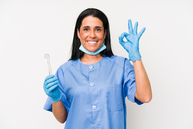 Dentist woman on white wall cheerful and confident showing ok gesture.