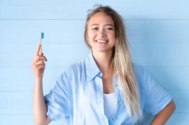 Женщина дантиста с бамбуковой зубной щеткой