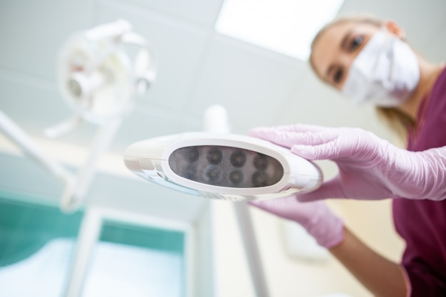 Dentist woman with uv lamp for teeth whitening