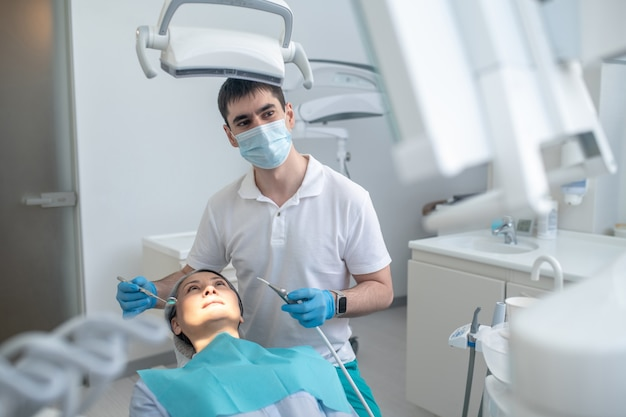 Dentist at work. male dentist working with a patient and making teeth restoration