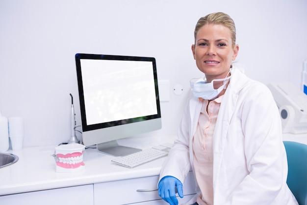 Стоматолог, сидя за компьютером в медицинской клинике