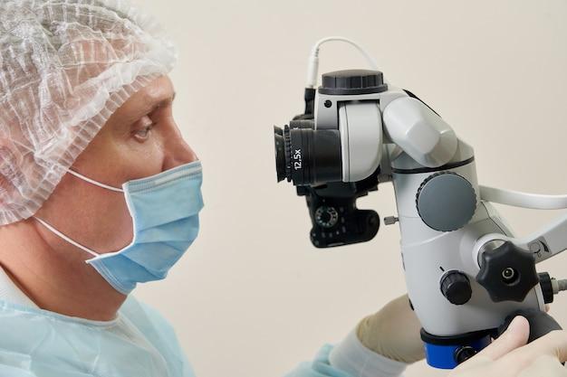 Стоматолог, работающий с стоматологическим микроскопом и пациент в современной стоматологической клинике