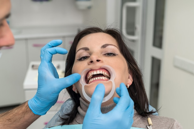 Dentist working with female patient close up