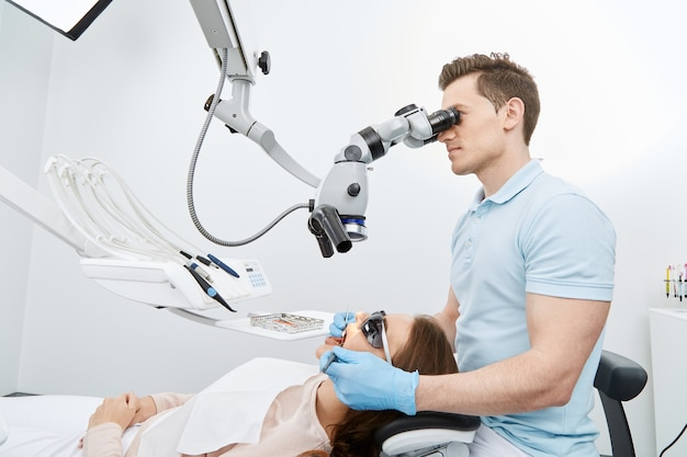 Dentist working with modern microscope